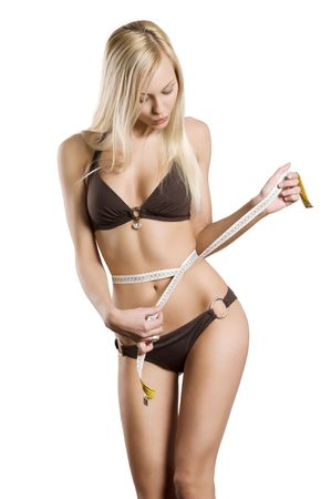 young blond woman measuring her body with a tape looking down and making face photo