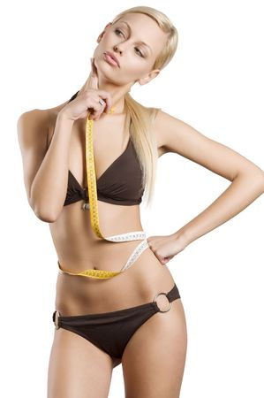 young blond girl in bikini with a tape around her waistline in act to think about her fitness body Stock Photo - 6681104
