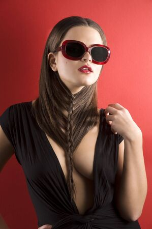 young brunette on red background wearing sunglasses and black dress with a creative hair stylish Stock Photo - 6681115