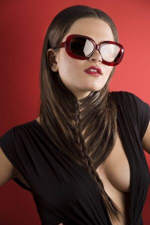 young brunette on red background wearing sunglasses and black dress with a creative hair stylish photo