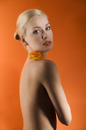 attractive and sensual young girl with an orange rose on her nacked shoulder looking in camera with stunning eyes  photo
