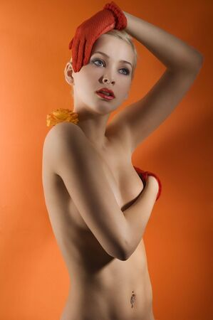 young and sensual nude woman with red gloves and a orange rose on her shoulder Stock Photo - 6710058