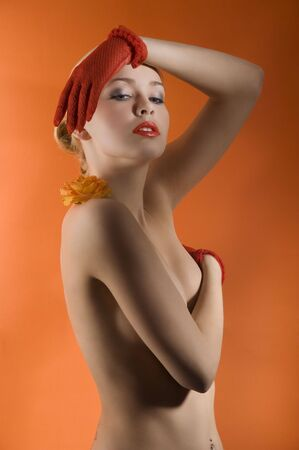 young and sensual nude woman with red gloves and a orange rose on her shoulder Stock Photo - 6710049