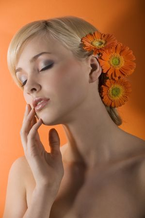 young beauty blond girl with closed eyes as dreaming with orange gerbera in hair photo