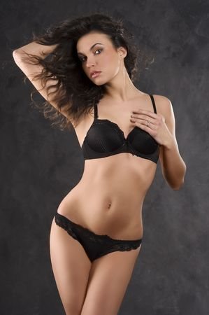 studio shot of a young, beautiful, sexy brunette woman in black lingerie with wind in her hair