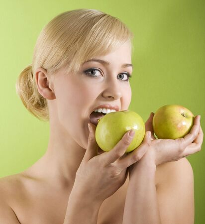 very cute blond girl in act to bite a green apple on colored background photo