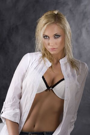 fashion portrait of a sexy blond girl in white shirt showing her bra on dark background with light effect Stock Photo - 6802110