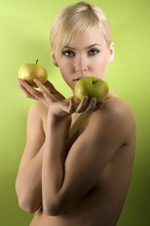 fashion and glamour shot of a nude young woman with apple on green background  photo