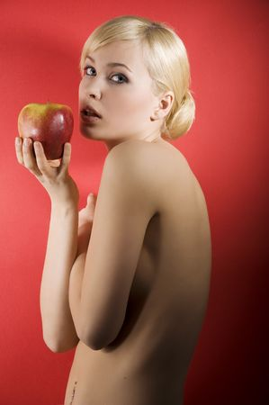 fashion shot of a glamour sensual girl with a red apple and nude body on red colored background photo