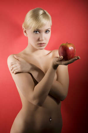 fashion shot of a glamour sensual girl keeping a red apple on red background  photo