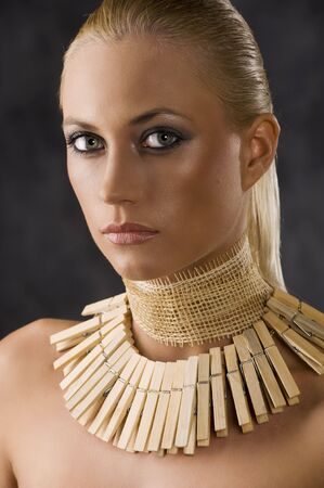 close up portrait of a beautiful blond woman with a creative necklace. looks like african style photo