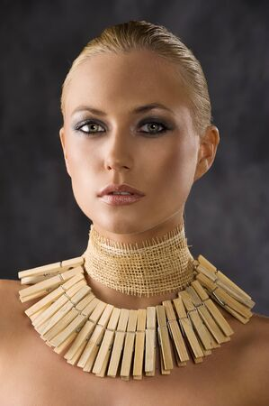 portrait closeup of attractive blond woman like an amazon with a necklace made of wood peg  photo