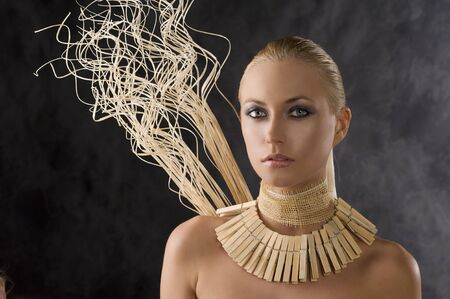 portrait on dark smoked background of beauty blond woman with necklace like an amazon  photo