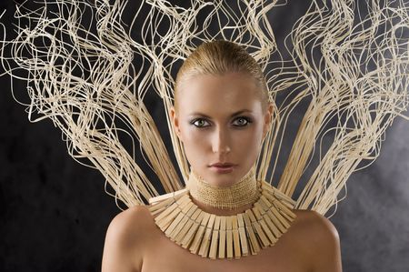beautiful portrait of attractive blond woman like an amazon with a necklace made of wood peg  photo
