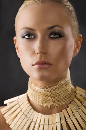 closeup portrait of attractive blond woman like an amazon with a necklace made of wood peg  photo