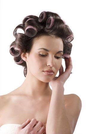 Mooie meisje met haar curlers op haar hoofd geïsoleerd op witte achtergrond  Stockfoto