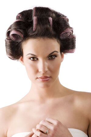 beauty portrait of a young brunette woman with hair curlers in her hair photo