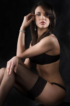 beautiful young brunette in lingerie and black stocking over dark background Stock Photo - 6933325