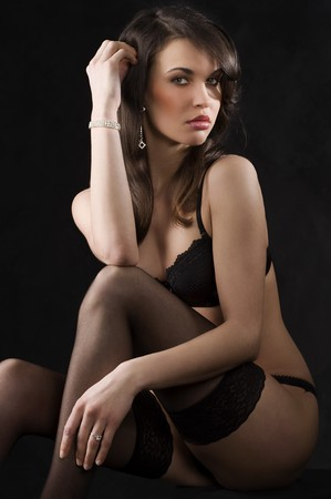 beautiful young brunette in lingerie and black stocking over dark background looking sensual in camera Stock Photo