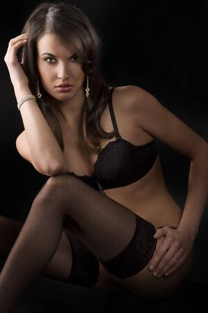beautiful young brunette in lingerie and black stocking over dark background Stock Photo - 6933332