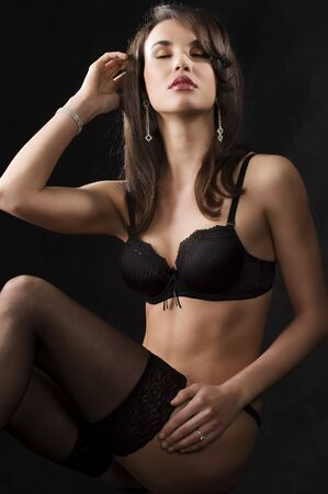 beautiful young brunette in lingerie and black stocking over dark background Stock Photo - 6933323