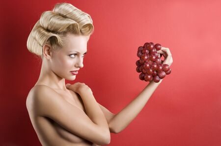 nice shot of Beautiful naked blond woman over red background looking a red grape  photo