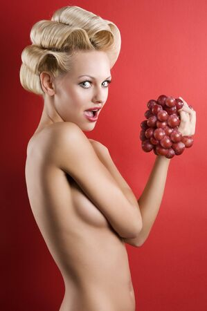 blond and graceful naked girl on red with some red grape Stock Photo - 6933351