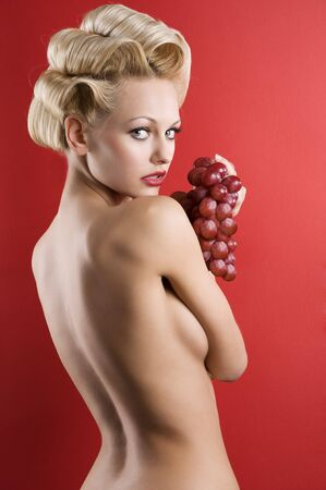 back side portrait of graceful blond nude woman with red grape on red background photo