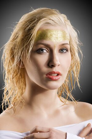 very cute blond girl with wet hair and a creative golden and shining make up on dark background photo