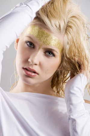nice portrait of young cute girl with shining gold make up taking pose photo
