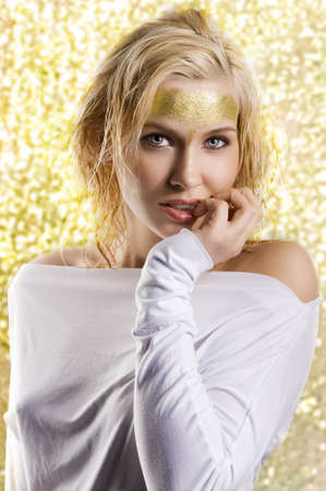 very cute blond girl with wet hair and a creative golden and shining make up photo