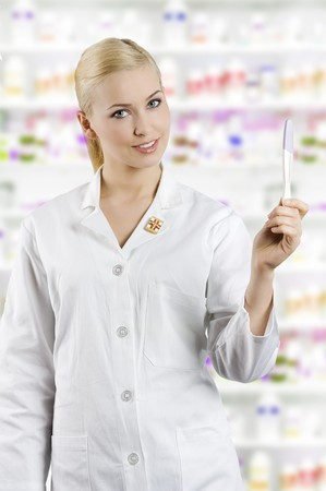 young blond woman as a nurse looking and showing a pregnant test Stock Photo - 7012730
