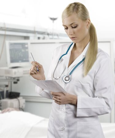 hospital gown: blond medical doctor woman with stethoscope Isolated over white background writing