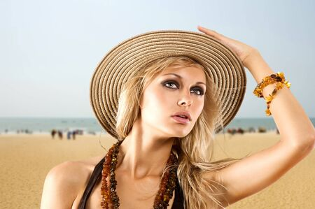 blond girl with summer hat on the beach with yellow warm sand photo