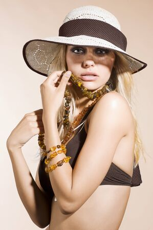 closeup portrait of pretty blond woman wearing a nice summer hat and natural jewellery photo
