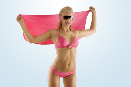 blond and attractive woman in pink bikini with sunglasses taking pose and playing with pareo Stock Photo - 7227008