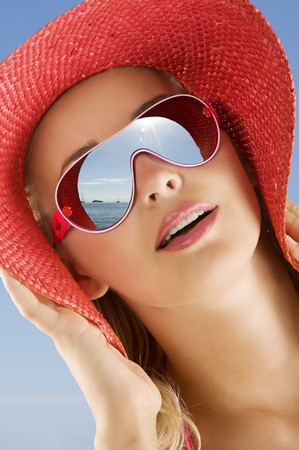 fine portrait of young cute woman with red summer hat and sun glasses looking at the sea in a sunny day photo