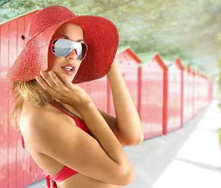 closeup portrait of pretty blond woman wearing a nice summer red hat and sunglasses Stock Photo - 7227048