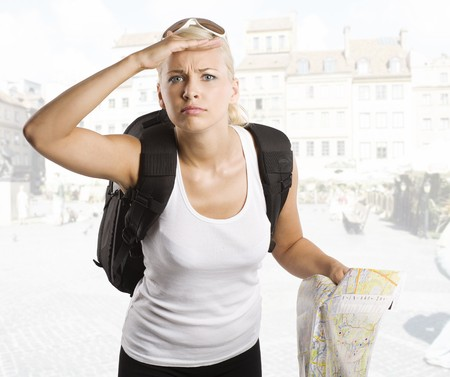 young pretty student girl in vacation looking for place on a map with rucksack photo