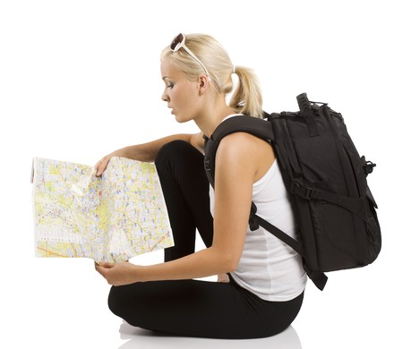 young pretty student girl in vacation sitting down and looking for place on a map photo