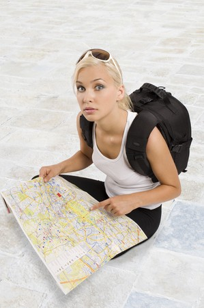 young pretty student girl in vacation with a map sitting down and looking in camera photo