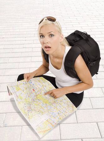 pretty girl in vacation with backpack sitting down with map and looking in camera surprised Stock Photo - 7240902