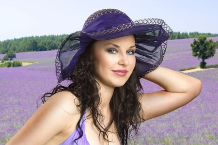 summmer shot portrait of a young smiling brunette woman wearing a blue hat with a lavender field as background photo