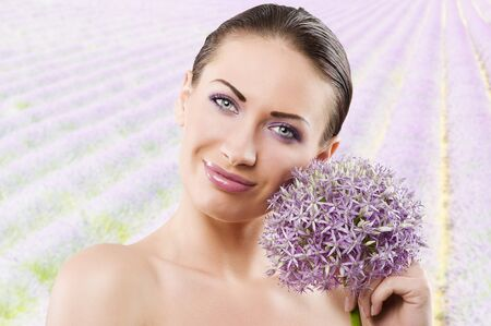 young and beautiful brunette woman in a beauty portrait with some purple flower near face photo