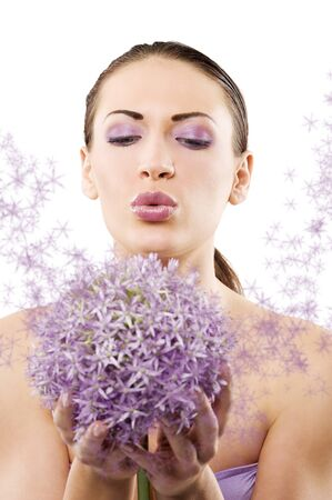 young and beautiful brunette woman in a beauty portrait blowing on purple flower  photo
