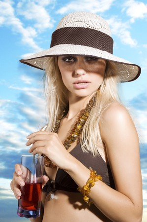 beauty portrait of graceful blond girl with summer hat and red drink  photo