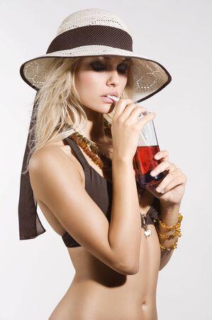 beach babe: bionda e sexy ragazza in bikini con un cappello di estate in atto a bere una bevanda rossa  Archivio Fotografico