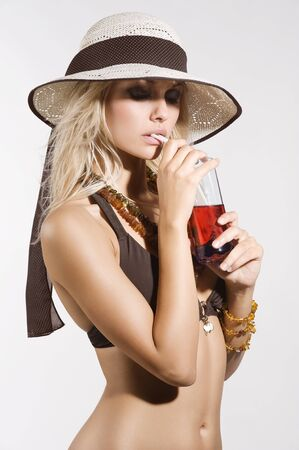 beach babe: blond and sexy girl in bikini with a summer hat in act to drink a red beverage