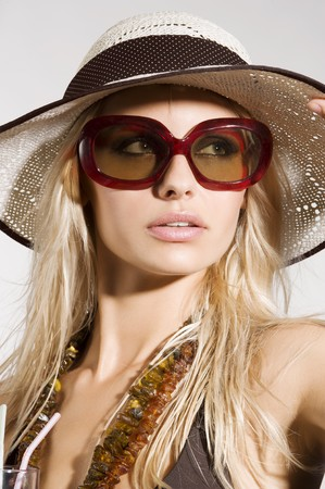 sunglasses beach: blond girl with summer hat and sunglasses posing and taking sun