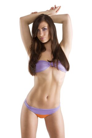 sexy and beautiful brunette woman in purple swimsuit bikini and long hair looking in camera Stock Photo